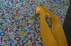 I stitched ribbon into the side seam so the letter learning bag can be tied closed.
